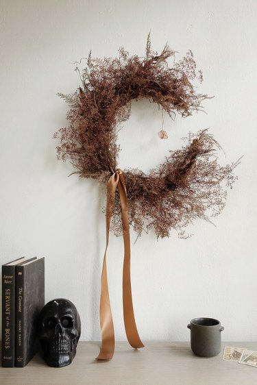 DIY crescent moon witch wreath with crystal on wall above Halloween decor