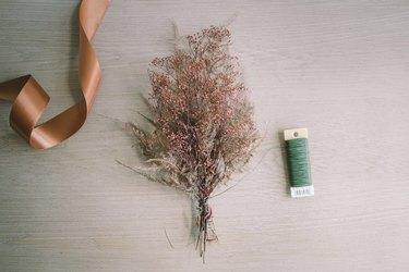 Dried gypsophilia and feather fern tied into a bundle with floral wire