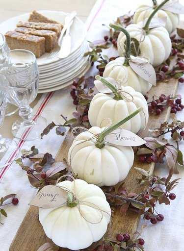 fall-inspired tablescape with mini white pumpkins and seasonal foliage