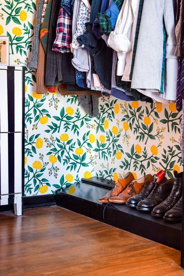 bedroom closet idea with floral wallpaper and clothes hanging on rod with shoes on floor rack