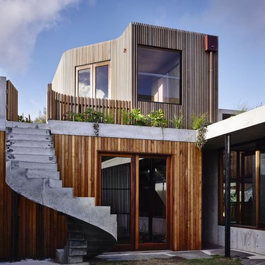 Contemporary home exterior with wood siding and winding staircase