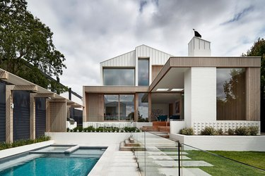 contemporary home exterior with an airy, coastal palette with pool in backyard