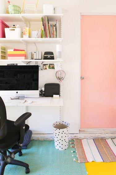 Garage office with pink door and computer on desk