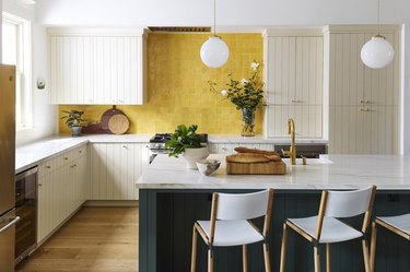 Large L-shaped kitchen with shiplap cabinets, yellow tile, marble countertops, and dark green island.