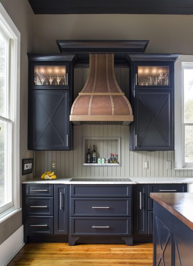Modern farmhouse kitchen with dark cabinets and steel hardware, gray shiplap, white countertop, rustic wood oven hood, and light hardwood floors