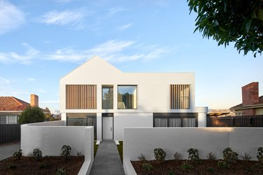 White contemporary home exterior with wood planks and minimalist features