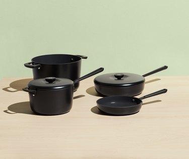 Black ceramic cookware set shown on green background