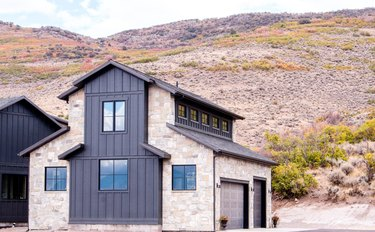 Contemporary home exterior with stonework and siding in mountain landscape