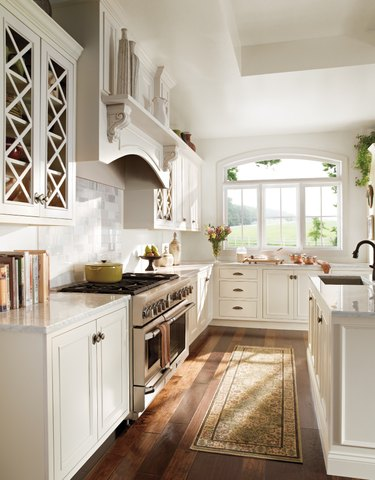 Farmhouse kitchen with off-white walls trim and cabinetry, and two-tone wood floors.