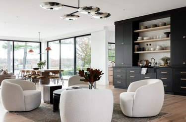 Four white lounge chairs, black built in wet Contemporary Bar, modern chandelier.