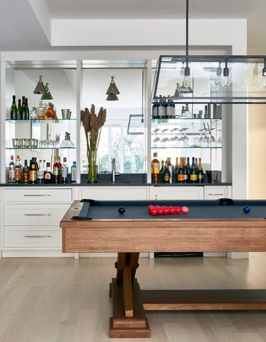 Pool table, built in Contemporary Bar with mirrors, hard wood floors.