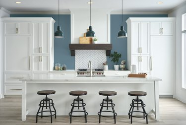 Modern farmhouse kitchen with white cabinetry, large island with wood barstool tops, pendant lighting, and accent blue wall