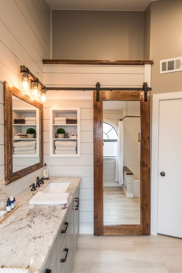 Wood Contemporary Barn Doors with full length mirror, white shiplap walls.