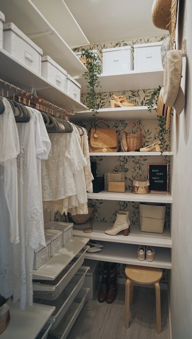 Wallpapered Bedroom Closet idea by Macarena Gea with open shelving on top of floral wallpaper