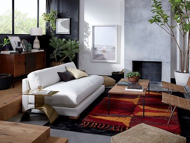 living room couch with large area rug and woven side chairs with brass side table