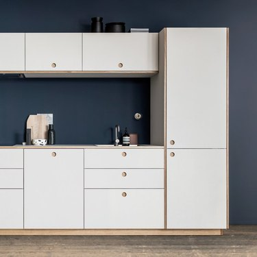 kitchen space with white cabinets and dark blue wall