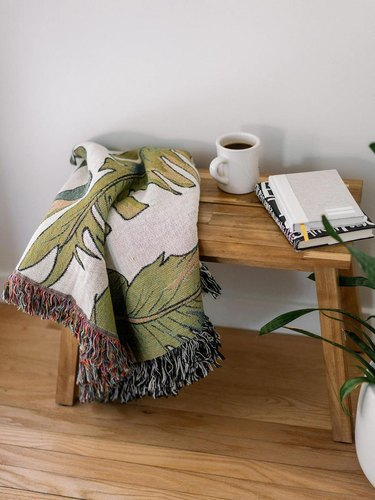 wood table with palm leaf print blanket