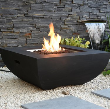 Black geometric fire table with fire, stone fence and waterfall