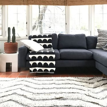 living room with dark couch and white rug and black and white blanket on top of the couch