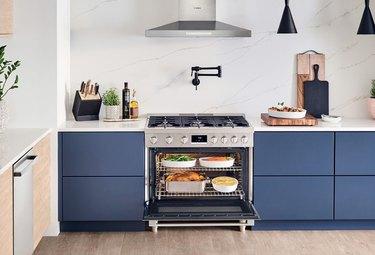 Freestanding Stainless Steel Gas Stove, pot filler, stainless hood, blue cabinets, white marble backsplash.