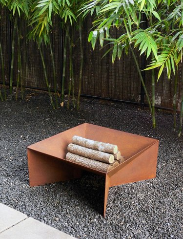 Geometric fire pit in rust sitting on gravel with logs