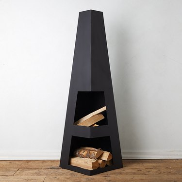 Obelisk-shaped contemporary fire pit with logs on white background
