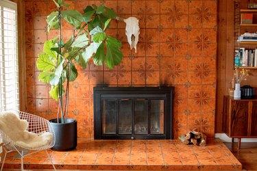 Orange tiled fireplace with large fiddle leaf fig tree