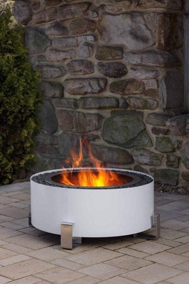 Sleek white contemporary fire pit against stonework