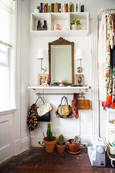 Purses hanging from a closet rod beneath a white shelf
