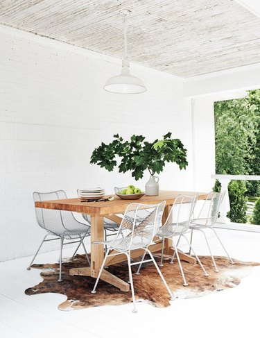 dining room with fresh foliage centerpiece and cowhide rug