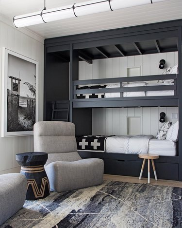 bedroom with shiplap walls and black built in bunk beds