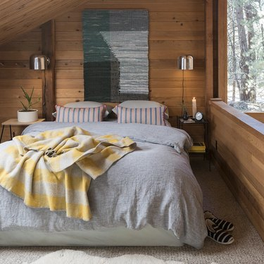 midcentury bedroom lighting idea with wall sconces on either side of bed