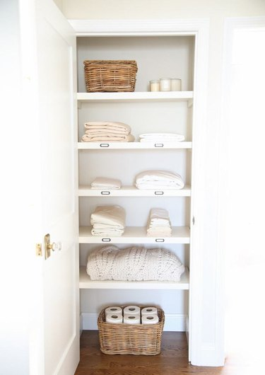 linen closet organization with labeled shelves and woven baskets