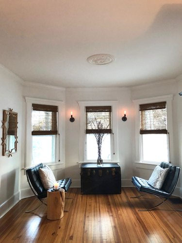 rustic living room lighting idea with wall sconces near windows and Barcelona chairs