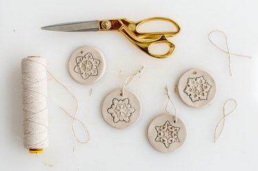 Pull string through the holes for hanging the finished ornaments.