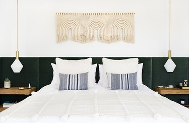 midcentury modern bedroom lighting idea with pendant lights over bedside tables with upholstered headboard