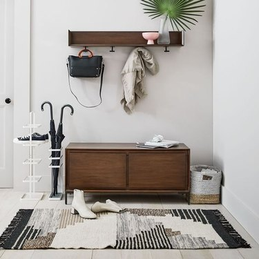 hallway with shelf and console and black and white rug