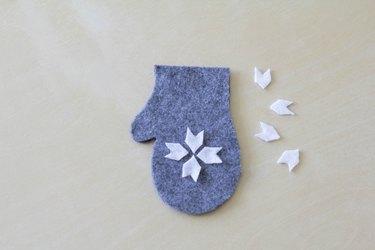 Gluing felt snowflake on top of mitten