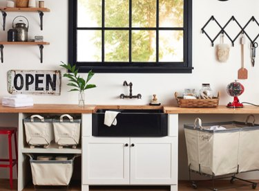 oil-rubbed bronze wall-mounted kitchen faucet and black farmhouse sink with wood countertops