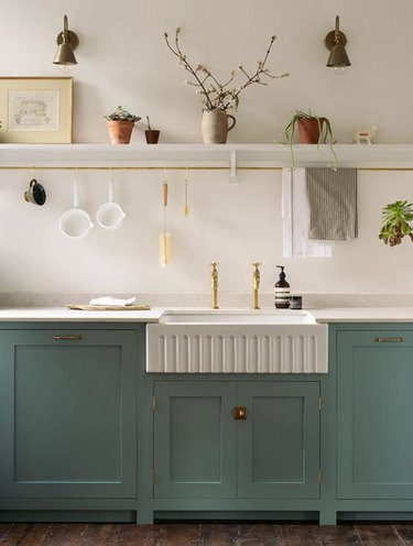 corrugated farmhouse kitchen sink and separate antique brass faucets with green cabinets