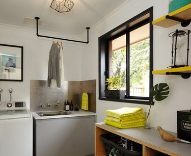 Garage Laundry Room with Washer, sink, clothes rack hanging over sink, shelves with towel.