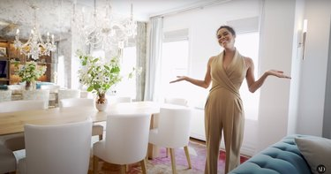 misty copeland standing in her dining area with wood table, white chairs, and a crystal chandelier