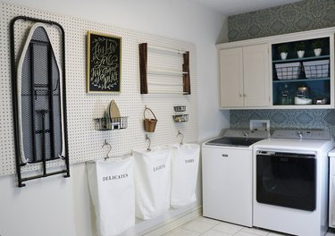 Garage Laundry Room with Peg board with laundry bags, ironing board, iron, chalkboard, clothes rack, washer dryer.