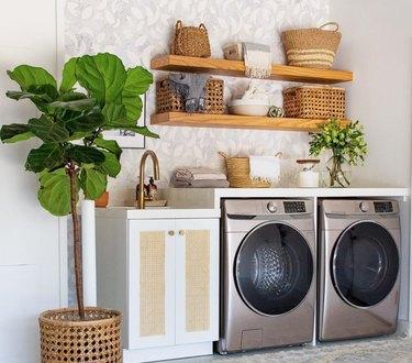 Garage Laundry Room with Stainless steel front load washer dryer, shelf, sink, open natural wood floating shelves, fiddle leaf fig, baskets.