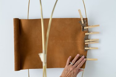 DIY magazine rack using gold hoops and leather