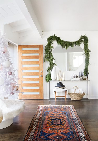 entryway with garland hung above mirror