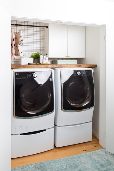 small basement laundry room ideas with white washer and dryer in a closet.