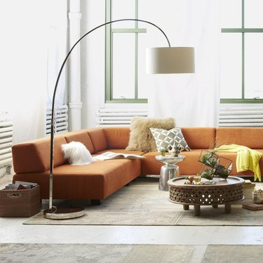 modern living room lighting idea with orange sofa and overarching lamp