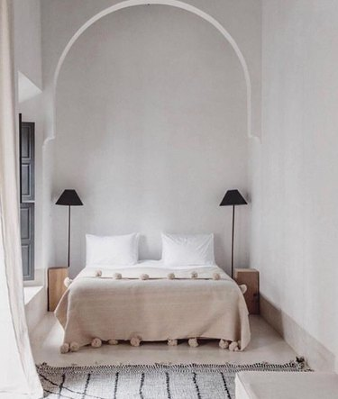 Scandinavian bedroom idea with arched detail, pair of black floor lamps, pom pom blanket