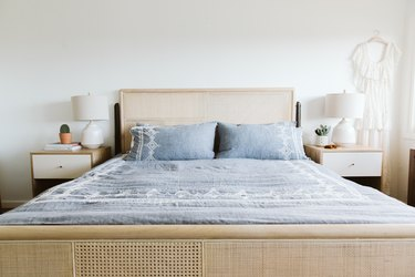 Bed with cane bed frame and headboard, and blue bedspread